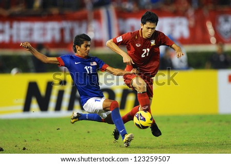 BANGKOK THAILAND-DECEMBER 13:Piyapol Bantao #21 of Thailand (red) run with the ball during the AFF Suzuki Cup between Malaysia and Thailand at Supachalasai stadium on Dec13,2012 in Bangkok,Thailand. - stock photo