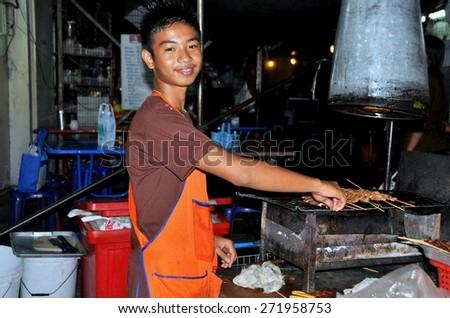 Bangkok, Thailand - December 15, 2009:  Smiling Thai youth grilling pork satay at a small restaurant on Sukhamvit Soi 11 road - stock photo