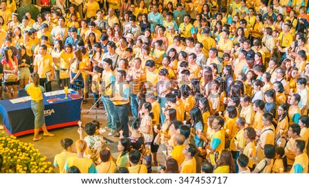 BANGKOK, THAILAND - DECEMBER 5, 2015: Thai People crowd wear yellow shirt, sing, celebrate, sign well-wishing book, selfie, candle-lighting ceremony His Majesty the King's 88th birthday, Father day - stock photo