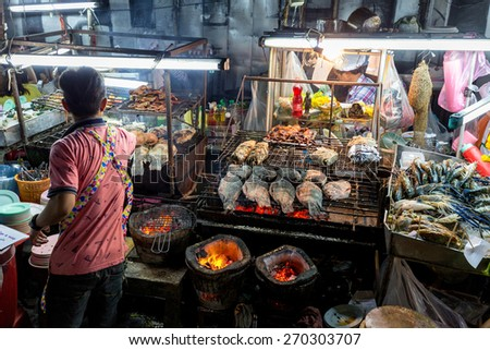 BANGKOK, THAILAND, DECEMBER 25, 2014: View on the outdoors kitchen of a street seafood restaurant in the Central World district in Bangkok, Thailand - stock photo