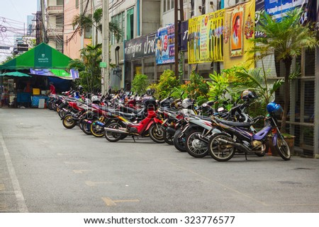 BANGKOK, THAILAND - FEB 20, 2015: Scooters parked along the street in town.  Motorbike is most popular and cheapest transport in Bangkok - stock photo