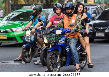 BANGKOK, THAILAND, February 15, 2015: A moto taxi is carrying a young Thai lady on his motorbike in the Sukhumvit road near the Thong Lor BTS station in Bangkok, Thailand - stock photo
