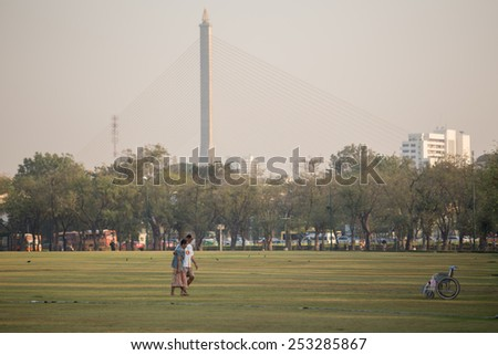 Bangkok, Thailand - February 7, 2015 : Husband older being help wives also fitness walking. He did it as a routine. The place is Sanamluang and background is Rama VIII Bridge. - stock photo