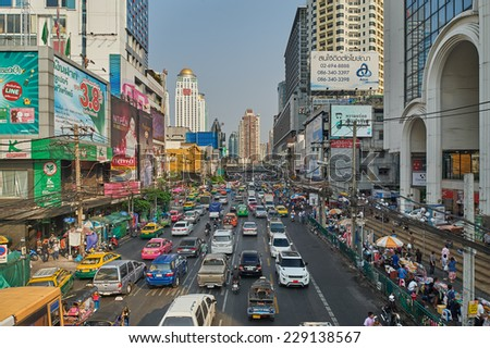 Bangkok, Thailand - February 26, 2014: Traffic moves slowly along a busy road on May 2, 2014 in Bangkok, Thailand. Annually an estimated 150,000 new cars join the already heavily congested streets. - stock photo