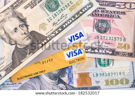 BANGKOK, THAILAND - FEBRUARY 21, 2014: Visa and Visa Electron credit cards and dollar bills. Visa Inc. is an american financial services corporation based in Foster City, California, United States. - stock photo