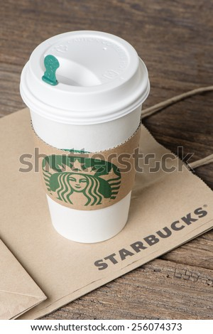 BANGKOK, THAILAND - FEBRUARY 26, 2015: White paper cup with sleeve with Starbucks logo. Starbucks is the world's largest coffee house with over 20,000 stores in 61 countries. - stock photo