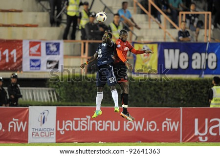 BANGKOK, THAILAND - JAN 11:  Frank Opoku Acheampong of the Buriram PEA(L)in action during the Thaicom FA Cup Final match  between MuangThong United at National Stadium on January11, 2012 in BKK Thailand. - stock photo