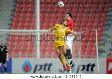BANGKOK THAILAND-JAN18:Kirati Keawsombut of Thailand (yellow) in action during the 41st King's cup  between Thailand and Norway at Rajamangala stadium on Jan 18, 2012 in Bangkok,Thailand. - stock photo