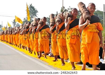 BANGKOK,THAILAND-JAN 26 : Row of Buddhist hike Thai monks on streets strewn with flower petals on the Thammachai hike establish the path of the great teachers on January 26,2015 in Bangkok , Thailand. - stock photo