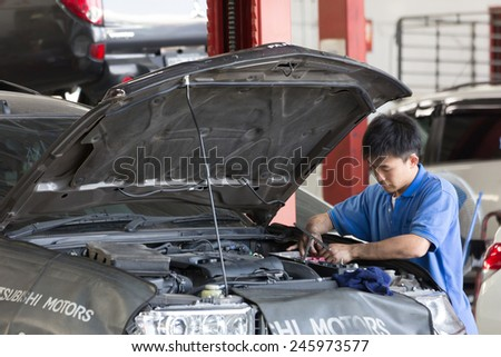 Bangkok, Thailand - January 21 : automobile mechanic examining car suspension of lifted  automobile at at Mitsubishi Motor Service station on January 21, 2015. Bangkok, Thailand. - stock photo