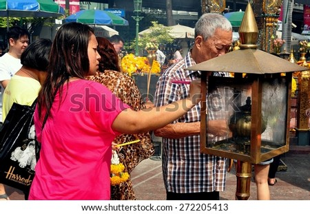 Bangkok, Thailand - January 25, 2013:  Elderly Thai man and a young woman lighting incense sticks from a flaming brass brazier at the Thao Maha Brahma Erawan Shrine - stock photo