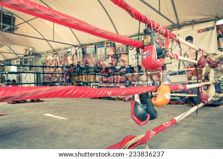 """BANGKOK, THAILAND - 25 JANUARY, 2014: gloves at training ring of Muay Thai; the combat sport uses stand-up striking with clinching techniques and is known as """"the art of eight limbs"""" - Vintage filter - stock photo"""