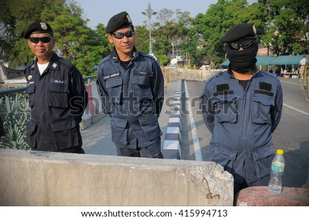 Bangkok, Thailand - January, 30, 2011: Police stand behind a barricade near the Thai Parliament during a political rally. - stock photo