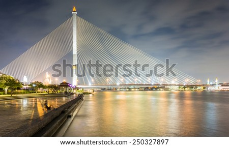 Bangkok, Thailand - January 9, 2015: Rama VIII Bridge, Rope Bridge across the Chao Phraya River and Cityscape of Bangkok; many people come to relax and exercise in this area.     - stock photo