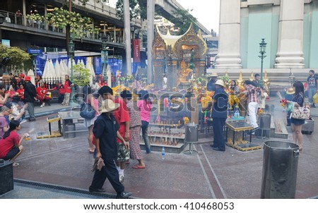 Bangkok, Thailand - January 9, 2011: Temple-goers visit the busy city centre Erawan Shrine. The landmark Hindu shrine was built in 1956 and has become a popular tourist attraction. - stock photo