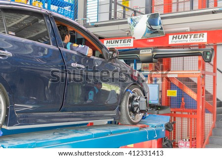 Bangkok, Thailand - January 16, 2016 : Unidentified serviceman checking suspension in a car at garage - stock photo