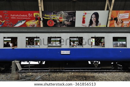 BANGKOK, THAILAND - JUL 26, 2013: Rail travelers ride a train at Bangkok Railway Station, known commonly Hua Lamphong. The station opened in 1916 and is the main rail hub of the Thai capital. - stock photo