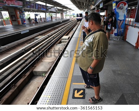 BANGKOK, THAILAND - JULY 17, 2013: Rail travelers wait for a train on a city centre train station platform. Launched in 1999, the BTS currently has a daily ridership of around 600,000 passengers. - stock photo