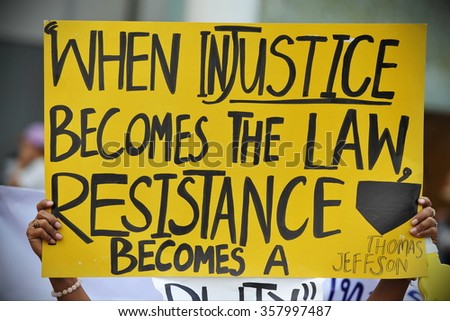 BANGKOK, THAILAND - JUN 30, 2013: A protester holds up a sign with a Thomas Jefferson quote at a large anti government rally in the Thai capital's shopping district. The protesters call for a coup. - stock photo