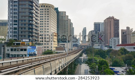 BANGKOK, THAILAND - MAR 22, 2015. A BTS Skytrain on elevated rails above Sukhumvit Road in Bangkok, Thailand. Each train of the mass transport rail network can carry over 1,000 passengers. - stock photo