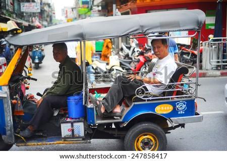 "BANGKOK, THAILAND - MARCH 27, 2012: Bangkok taxi ""Tuk-tuk"" with passengers in traffic jam. There are more than 100,000 ""tuk-tuk"" in Bangkok.  - stock photo"