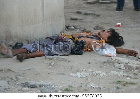 BANGKOK, THAILAND - MARCH 18: Thai homeless man sleeps by the roadside on March 18, 2009 in Bangkok. - stock photo