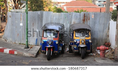 BANGKOK, THAILAND - MARCH 8,2014: Tuk-tuk moto taxi parking on the street to wait passengers. Famous bangkok moto-taxi called tuk-tuk is a landmark of the city and popular transport. - stock photo