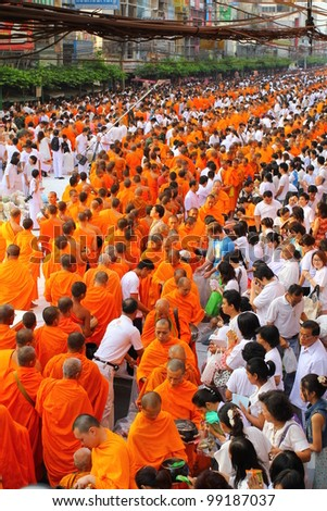 BANGKOK , THAILAND - MARCH 18: unidentified people give food offerings to Buddhist monks on March 18, 2012 Pratunam in Bangkok, Thailand. Thai traditional Ceremony: BuddhaJayanti 2600 years - stock photo
