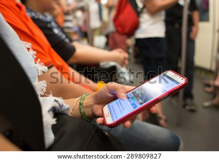 BANGKOK, THAILAND- MARCH 16: Unknown people uses mobile phone while travel by subway on March 16, 2015 in Bangkok, Thailand. It's a people's behavior to entertain when they take public transportation. - stock photo