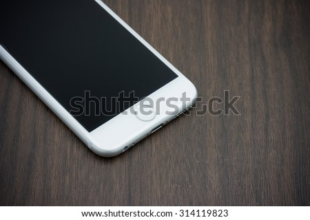 BANGKOK, THAILAND - MAY 7, 2015. Apple Iphone 6 in white color with blank screen laying on wooden table. - stock photo