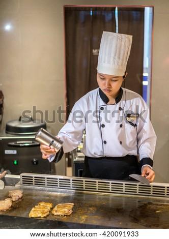 Bangkok, Thailand - 7 May 2016 - Female chef seasons delicious chicken teriyaki to serve the customer in a teppanyaki kitchen. - stock photo