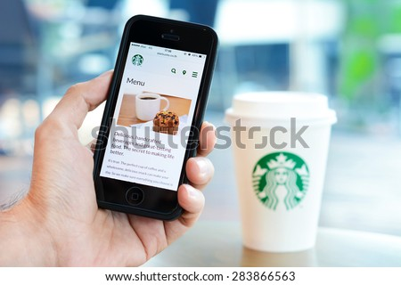 Bangkok, Thailand - May 20, 2015 : Hand holding smart phone opening online menu page of Starbucks  website, with blur Starbucks coffee cup background, in Starbucks coffee shop. - stock photo