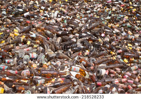 Bangkok, Thailand - 15 May 2014:  Mountain of used glass bottles in a recycling plant  May 15,  2014 in Bangkok. The used glass was collected in containers and will be crashed for recycling. - stock photo