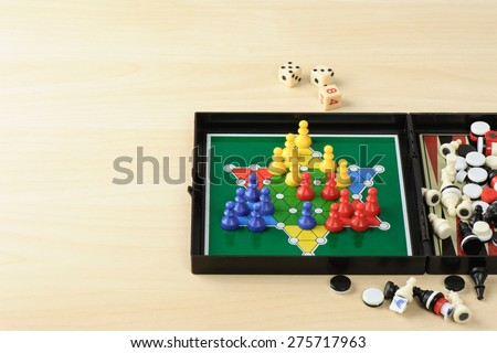 BANGKOK, THAILAND - MAY 07, 2015: Playing mini Chinese checkers in multi games in one box on wooden desk with space for adding text. - stock photo