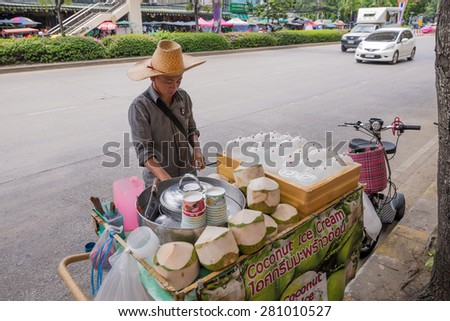 Bangkok, Thailand - May 23, 2015 Unidentified man is selling coconut juice and ice cream on street at Jatujak, the biggest weekend market in South East Asia. - stock photo