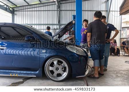 Bangkok, Thailand - May 15, 2016 : Unidentified serviceman checking a car for fix and repair at garage - stock photo