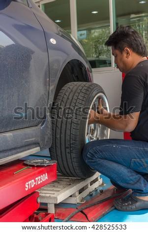 Bangkok, Thailand - May 20, 2016 : Unidentified serviceman checking suspension in a car at garage - stock photo