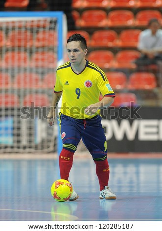 BANGKOK, THAILAND-NOV 18: Andres Reyes of Colombia (y) runs with the ball during the FIFA Futsal World Cup between Italy and Colombia at Indoor Stadium Huamark on Nov18,2012 in Bangkok,Thailand. - stock photo