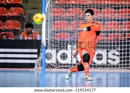 BANGKOK,THAILAND-NOV18: Goalkeeper Juan Lozano  (yellow ) of Colombia shoot the ball during the FIFA Futsal World Cup  between Italy and Colombia at Indoor Stadium Huamark on Nov18,2012 in,Thailand. - stock photo