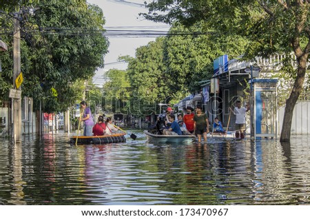 Bangkok - Thailand, Nov 6, 2011: People with their transportation at Soi Chinnakhet, Ngamwongwan road during a big flooding in Thailand. - stock photo