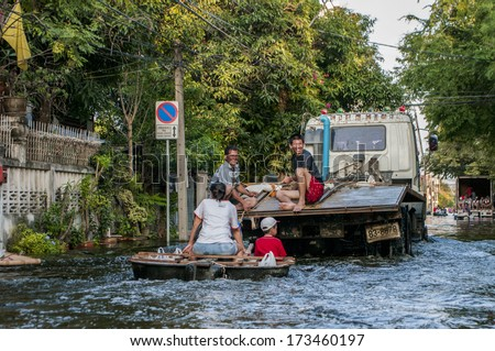 Bangkok - Thailand, Nov 6, 2011: People with their transportation during a big flooding in Thailand. At Soi Chinnakhet, Ngamwongwan road. - stock photo