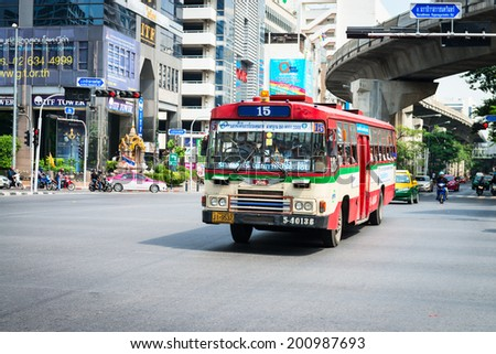 BANGKOK, THAILAND - 21 NOV 2013: Public transport bus passes crossroads street with skytrain track on background - stock photo