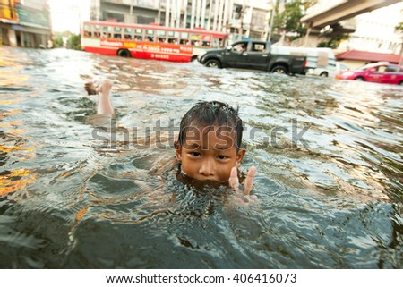 BANGKOK , THAILAND - NOVEMBER 2, 2011 :  Bangkok, Thailand 2011 during the big floods that affected several provinces of the country. Children enjoy flooded streets to bathe with big health risks.  - stock photo
