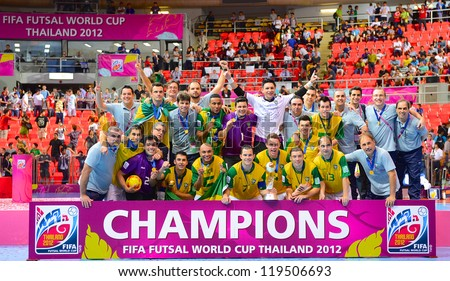 BANGKOK,THAILAND-NOVEMBER18:Brazil players and support staff pose for a photo with the trophy  after winningthe FIFA Futsal World Cup Final at Indoor Stadium Huamark on Nov18,2012 in Bangkok,Thailand. - stock photo