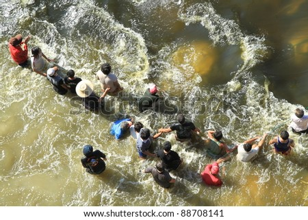 BANGKOK, THAILAND - NOVEMBER 13: Group of men destroying water barrier to open the water flow to opposite during the worst monsoon flooding in decades in Bangkok, Thailand on November 13, 2011. - stock photo