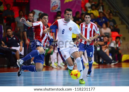 BANGKOK,THAILAND-NOVEMBER 4:Jorge Arias(white)of Costa Rica for the ball during the FIFA Futsal World Cup between Paraguay and Costa Rica at Indoor Stadium Huamark on Nov4, 2012 in Bangkok, Thailand. - stock photo
