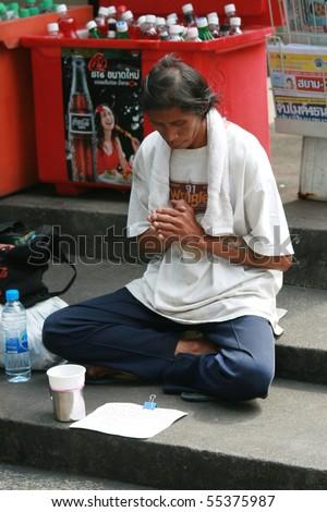BANGKOK, THAILAND - NOVEMBER 29: Thai man sits for money by the road on November 29, 2008 in Bangkok. - stock photo