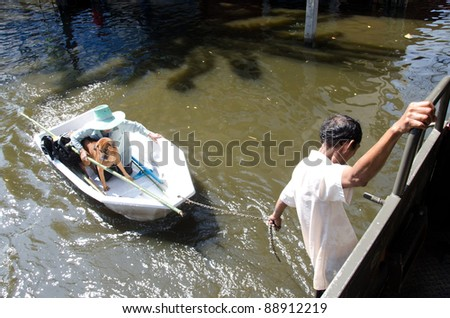 BANGKOK, THAILAND-NOVEMBER 13: Transportation of people in the streets flooded after the heaviest monsoon rain in 50 years in the capital on November 13, 2011 Phahon Yothin Road, bangkok, Thailand. - stock photo