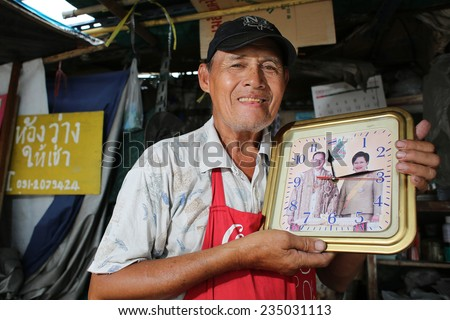 BANGKOK,THAILAND- NOVEMBER 29: Unidentified thai man showing picture of King Bhumibol and Queen Sirikit on November 29, 2014 in Bangkok, Thailand. King Bhumibol is respected and revered by most Thais. - stock photo