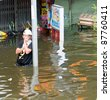 BANGKOK, THAILAND - OCTOBER 29: Woman using here mobile phone in a flooded street during the worst flooding in decades in Bangkok, Thailand on October 29, 2011. - stock photo